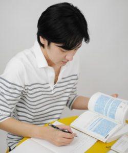 本を読んでノートに書く男性